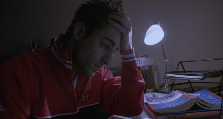 Drew Dawson (Luke Guldan) holding his forehead while studying